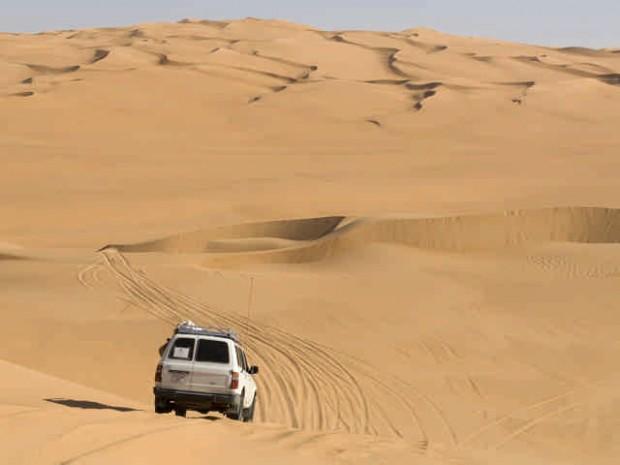 SUV on sand dunes, Erg Awbari, Sahara desert, Fezzan, Libya.